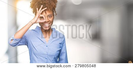 Beautiful young african american business woman over isolated background doing ok gesture with hand smiling, eye looking through fingers with happy face.