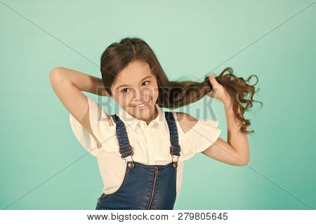 Girl hold long hair on blue background. Child smile with healthy brunette hair. Haircare, hairstyle concept. Beauty or hairdressing salon, punchy pastel poster