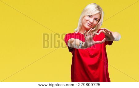Young beautiful blonde woman wearing red t-shirt over isolated background smiling in love showing heart symbol and shape with hands. Romantic concept.