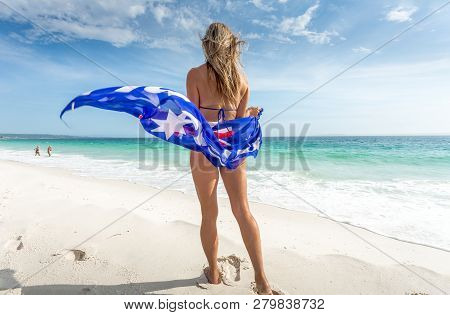 A Woman Stands On The Beach With Australian Flag Sarong Flapping In The Wind On A Glorious Sunny Sum