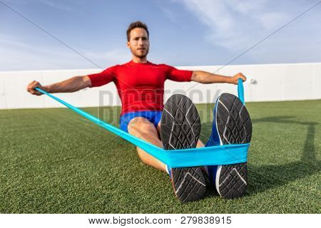 Fitness man training arms with resistance bands at outdoor gym or home garden. Body workout with equipment outside. Elastic rubber band accessory.