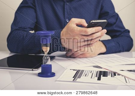 Hourglass. Businessman Working In The Office In The Background. Concept Time Is Money.
