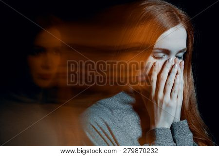 Blurred picture of young beautiful redhead girl with depression covering her mouth poster