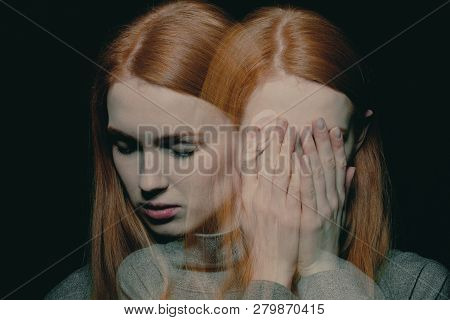 Pretty young redhead girl with anxiety disorder hiding her face, mental disorder concept poster