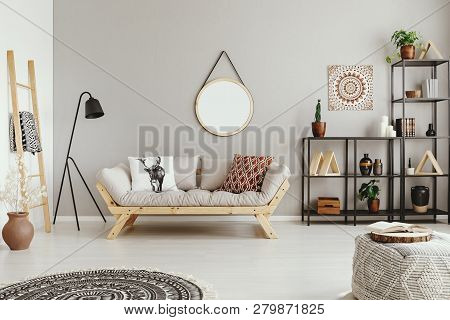 Light Grey Living Room Interior With Mirror On The Wall, Couch With Cushions And Metal Rack With Dec