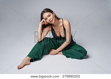 Sensual Brunette Female In Green Trousers And Top With Deep Cleavage