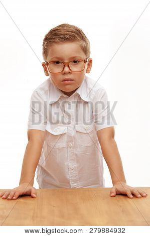 A Clever Cute Boy Answers At School By Giving The Correct Answer On A White Background. Concept Of G