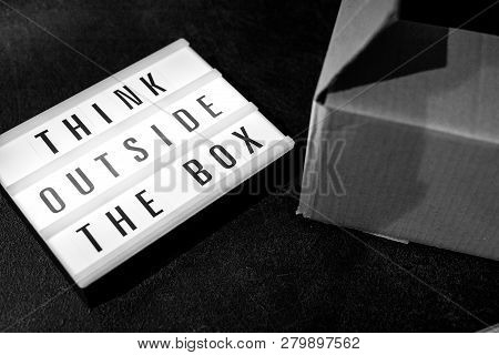 Think Outside The Box Message On Lightbox On Top Of Open Parcel, Concept Of Being Unique For Success