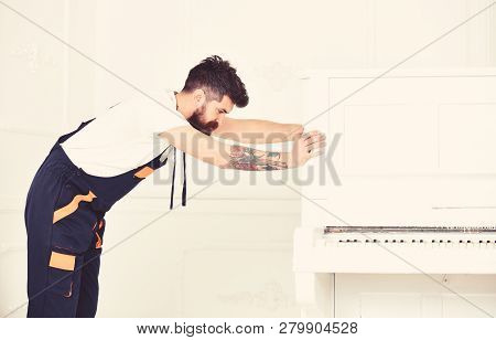 Man With Beard And Mustache, Worker In Overalls Pushes Piano, White Background. Delivery Service Con