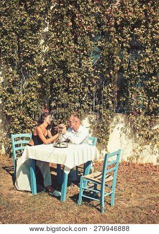Couple In Love At Outdoor Cafe. Proposal And Marriage Concept. Man Kiss Hand Of Girl In Restaurant.