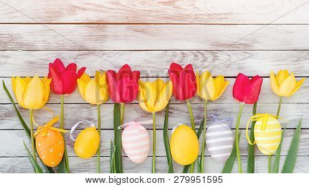 Easter Eggs And Tulips. Happy Easter Card With Copy Space. Colorful Easter Eggs Among Fresh Spring T