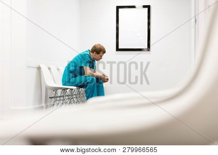 Thoughtful nurse in uniform sitting on chair at hospital corridor
