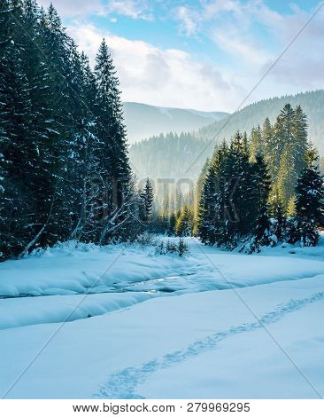 Winter Landscape With River In Mountains. Beautiful Nature Scenery With Snow Covered Riverbank Among