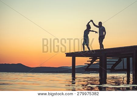 Couple In Love Dance On Sunrise Beach. Summer Holiday And Travel Vacation. Girl And Man At Sea Water