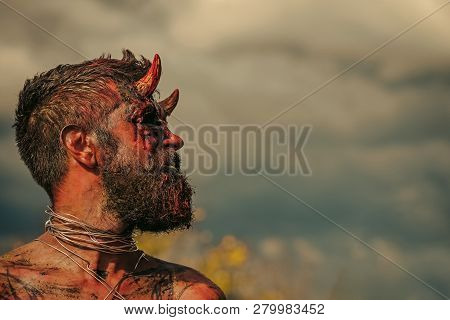 Halloween temptation, hell, evil, horror, darkness concept. Satan with red blood and wounds on face skin. Dragon creature on cloudy sky. Demon man with beard. Devil head with bloody horns, copy space poster