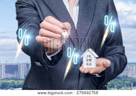 A Businesswoman In Suit Is Holding A Key And A House Model On Her Palm With Percent Icons At Foregro