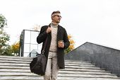 Image of handsome man 30s wearing eyeglasses walking through city street and holding takeaway coffee poster