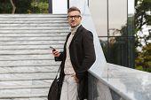 Image of caucasian man 30s wearing eyeglasses walking through city street and using smartphone poster