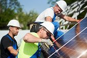 Three professional technicians installing solar photo voltaic panel to metal platform on blue sky background. Stand-alone solar system installation, efficiency and professionalism concept. poster