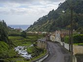 Road in old small village Faial da Terra with cascading river and sea horizon, Sao Miguel, Azores poster