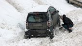 Man digging up up stuck in snow car. Car wheel stuck in the snow. Driving in adverse weather conditions. How to dig your car out of snow. poster