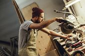 Side view of adult guy in apron using circular saw to cut piece of lumber on workbench in joinery poster