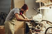 Side view oh handsome adult man standing near workbench and cutting piece of wood with circular saw in joinery poster