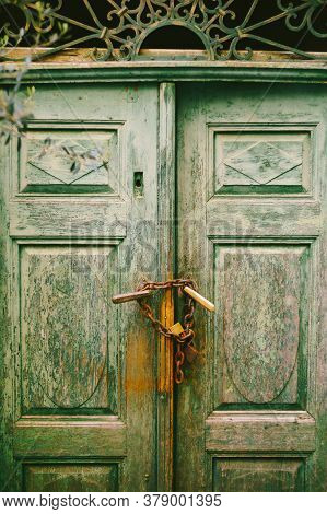 Close-up Of Closed Doors Of Shabby Green Color With Bandaged Chains And Locked Door Handles.