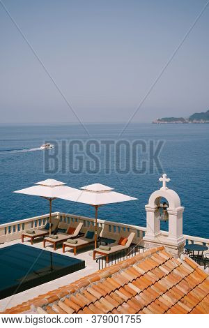 Wooden Sun Loungers Under White Beach Umbrellas, Near The Pool And Church, Overlooking The Sea. Svet
