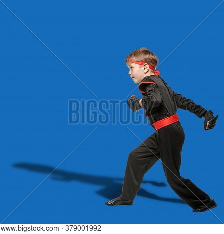 Young Karate Boy Practicing Fighting Position On Blue Background