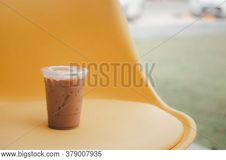 Iced Mocha In Plastic Cup On Yellow Table At Garden Cafe Restaurant In Hot Sunny Day