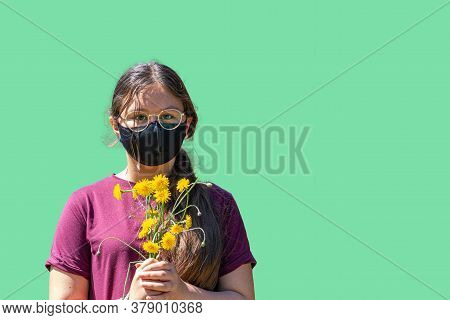 A Young Preteen Girl Wearing A Black Face Mask, Looking Straight Into The Camera, Holds A Bouquet Of