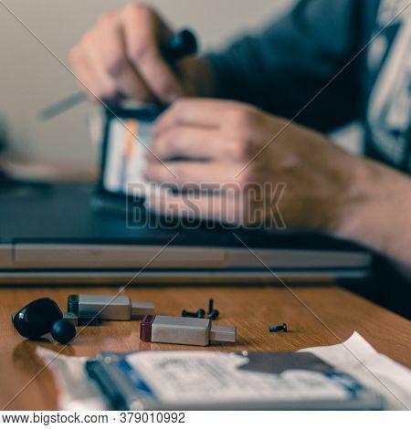 Male Technician Fixing Broken Laptop At Home, Closeup Photo