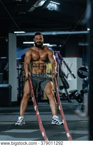 Fit Athletic Bodybuilder Pulling Heavy Battle Rope