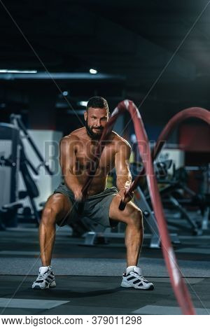 Portrait Of Strong Muscular Man Pulling Heavy Rope In Gym
