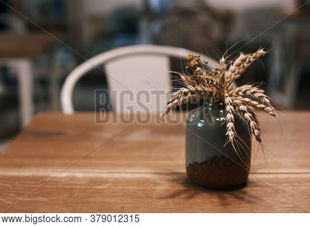 Hygge Home Decor Concept. Small Ceramic Vase With Dried Wheat Spikes Standing On The Table. Toned Sh