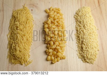 Different Types Of Raw Soup Pasta On Light Wooden Table. Pasta Types; Noodles, Tiburón And Little St