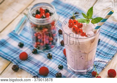 Non-alcoholic Milkshake Smoothie With Fresh Currant, Raspberry And Mint Leaves On A Wooden Backgroun