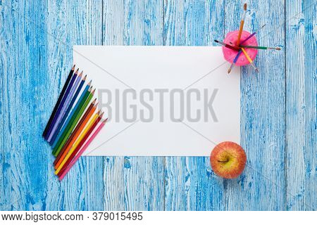 Blank sheet, colored pencils and paint brushes on blue wooden background. Top view, copy space. School accessories for children's education and development. Art lesson or drawing