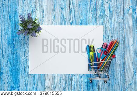 Shopping trolley, stationery accessories and blank sheet on blue wooden background. Top view, copy space.  School accessories for education and development. Preparation for school