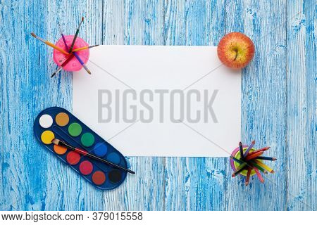 Blank sheet, colored pencils, paints and paint brushes on blue wooden background. Top view, copy space. School accessories for children's education and development. Art lesson or drawing