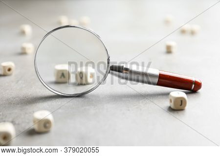 View On Cubes With Letters A And Q Through Magnifying Glass At Light Grey Stone Background, Closeup.