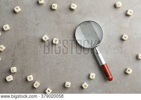 Magnifier Glass And Cubes With Letters On Light Grey Stone Background, Flat Lay. Find Keywords Conce