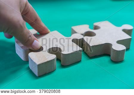 Hands Holding Jigsaw Puzzle Pieces For Teamwork On Green Paper Background, Teamwork Put Pieces Toget