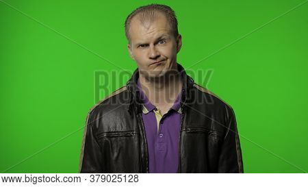 Aggressive Brutal Rocker Man In Brown Leather Jacket Looking With Crazy Expression. Portrait Of Guy
