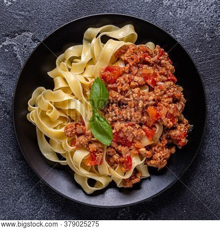 Traditional Italian Pasta Bolognese On A Black Plate, Top View.