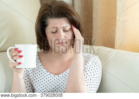 Woman With A Headache And A Cup Of Tea