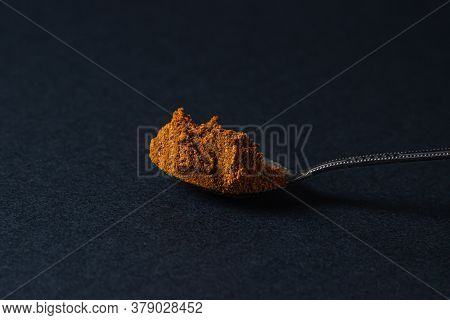 Red Ground Pepper On A Black Background. A Spoonful Of Red Ground Pepper. Spicy Seasoning