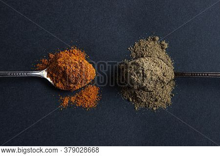 Red And Black Ground Pepper On A Black Background. The Spoon With Black Pepper Lies Next To The Spoo