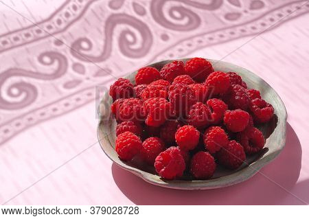 Raspberries Are Fresh, Red On A Ceramic Plate On A Pink Background And With An Openwork Shadow. Clos